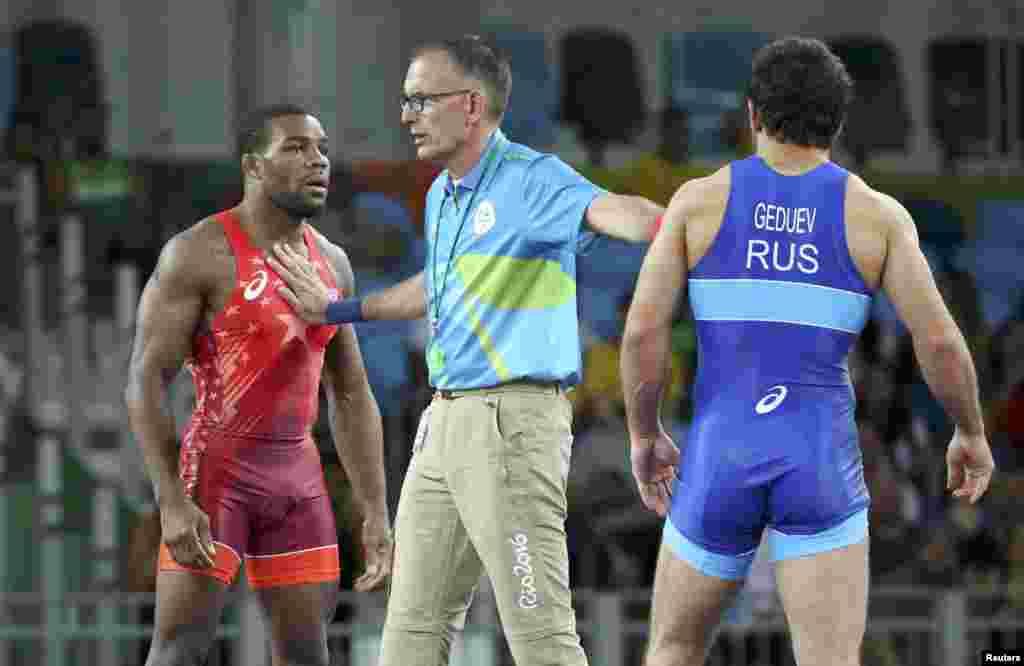 The referee separates the United States' Jordan Burroughs (left) and Aniuar Geduev (Russia) in the men's freestyle wrestling 74-kilogram quarterfinal. Geduev later went on to win the silver medal.