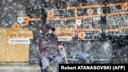A woman waits for public transport at a bus stop during heavy snowfall in Skopje on April 1.