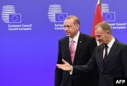 Turkish President Recep Tayyip Erdogan (left) is welcomed by European Council President Donald Tusk at the European Council in Brussels on October 5.