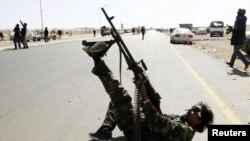 Ливийский повстанец ведет огонь по самолетам Каддафи