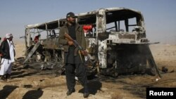 A Pakistani paramilitary soldier stands guard at the site of the bus bombing in Balochistan on December 30.