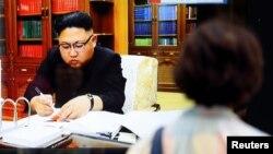 شهروندان در ژاپن در حال تماشای اخبار مربوط به انجام آزمایش موشک قارهپیما توسط کره شمالی هستند؛ بر صفحه تلویزیون تصویر رهبر کره شمالی دیده میشود