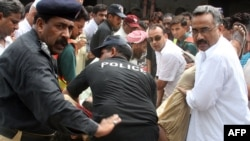 Pakistani security officials carry the bodies of two Christians killed outside a court in Faisalabad on July 19.
