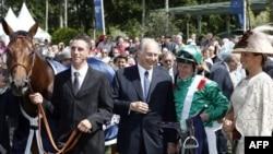 Ага Хан (сол жақтан екінші) және ханшайым Зара Ага Кан (оң жақта) ирланд шабандозы Джон Патрик Муртагты жеңісімен құттықтап жатыр. Франция, Шантильи, 17 маусым 2012 жыл.