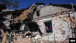 Село Пески: женщина смотрит в окно дома, разрушенного в результате обстрелов