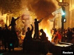 """""""Окленди ээле!"""" деп аталган демонстрация учурунда анын катышуучулары байрактарды булгалап, автомобилдин дөңгөлөктөрүн өрттөшүүдө. Калифорния, Окленд. 3-ноябрь 2011"""
