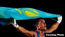 Олимпийский чемпион по боксу Серик Сапиев держит над головой флаг Казахстана. Лондон, 12 августа 2012 года. Фото с сайта Facebook.
