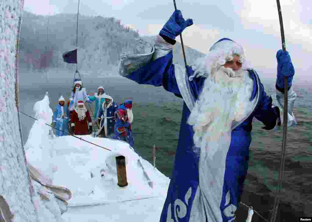 Members of the Skipper yacht club dressed as Ded Moroz, the Russian equivalent of Santa Claus, and his granddaughter Snegurochka (Snow Maiden) sail on a yacht along the Yenisei River while marking the end of the sailing season, outside the Siberian city of Krasnoyarsk, Russia. (Reuters/Ilya Naymushin)