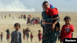 Displaced people from the minority Yazidi sect, flee violence from Islamic State (IS) militants in the town of Sinjar in northern Iraq in August 2014.