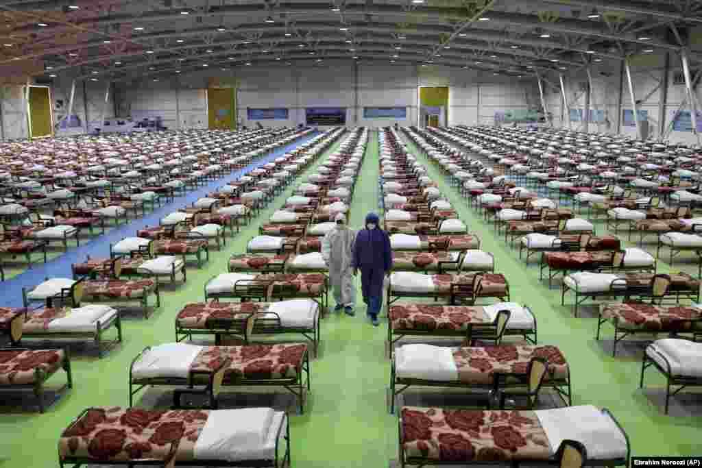 Ирански работници в защитно облекло във временната болница за пациенти с COVID-19. На 26 март Международният изложбен център в столицата Техеран беше превърнат в болница с капацитет 2000 легла.