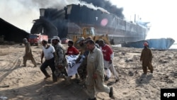 Pakistani security officials carry the body of one of the victims killed after an explosion at the Gadani ship-breaking yard on November 1.
