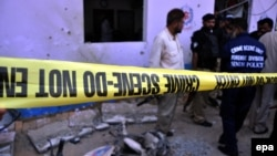 Security officials inspect the site of a bomb blast that targeted a police checkpoint in Karachi. (file photo)