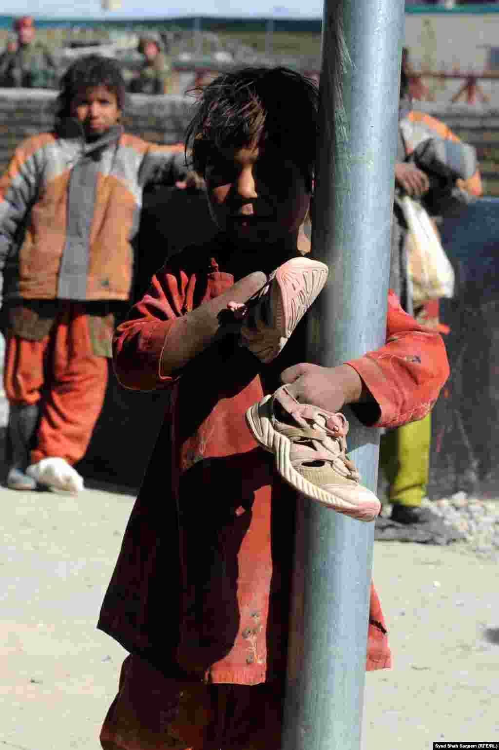 افغانستان: کندهار، یوه وړکې افغان انجلۍ پر یوې ستنې لاسونه راجاروستي دي