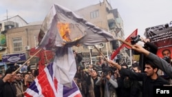 تظاهرات گروهی در تهران مقابل سفارت بریتانیا که در آن پرچم این کشور آتش زده شد.