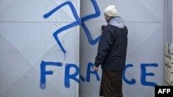 Верующий открывает дверь во двор мечети, на которой нацистские граффити. Лион, Франция, 20 декабря 2011 года.