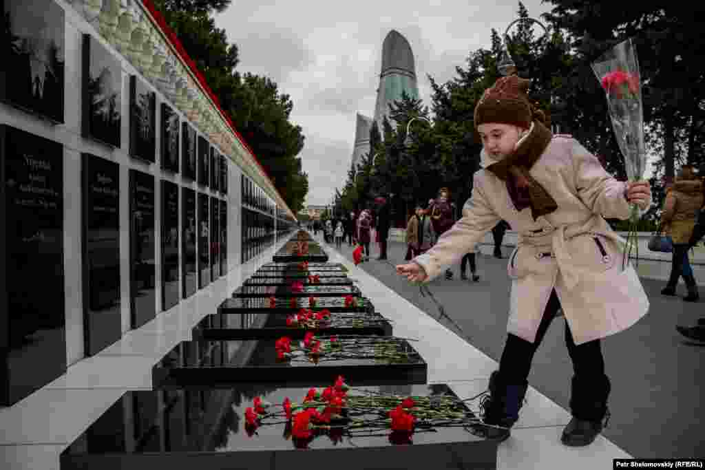A girl lays flowers at the Alley of Martyrs memorial