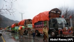 Pakistani Kashmiris walk past India-bound cargo trucks, parked as road is closed to Indian Kashmir, in the border town of Chakoti at Line of Control in Pakistani Kashmir, February 26, 2019
