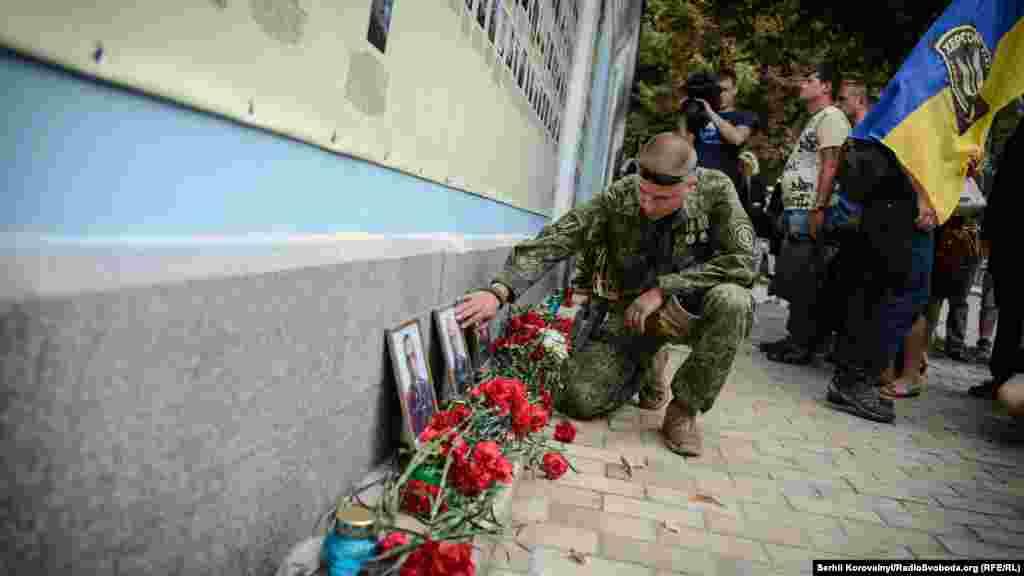Боєць батальйону «Донбас» схилився над фотографією товариша, якого він втратив в «Іловайському котлі»