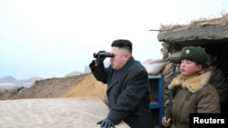 Северокорейский лидер Ким Чен Ын смотрит в бинокль в сторону Южной Кореи во время визита в военные части на границе, 7 марта 2013 года.