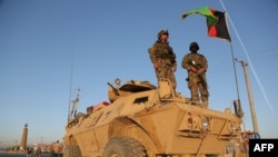 Afghan security personnel stand guard on an armored vehicle at a checkpoint in Ghazni on October 13.