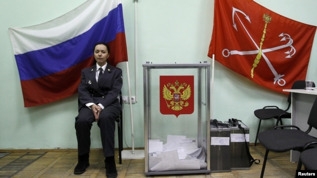 A police officer sits next to a ballot box at a polling station in St. Petersburg on March 4. The OSCE says the vote count was faulty in almost one-third of the polling stations observed.