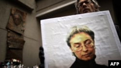 A man holds a portrait of slain Russian journalist Anna Politkovskaya during a rally marking the eighth anniversary of her death in Moscow on October 7, 2014.