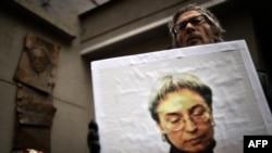 """Мужчина с портретом Анны Политковской во время акции в память об убитом журналисте """"Новой газеты"""". Москва, 7 октября 2015 года."""
