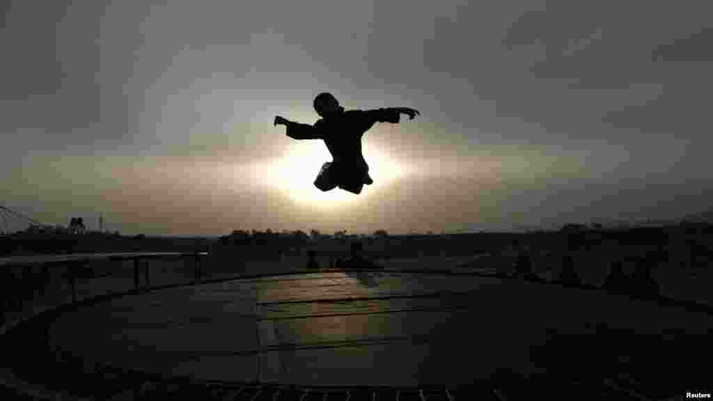 A boy is silhouetted against the sun while jumping on a trampoline on the outskirts of the Pakistani capital, Islamabad. (Reuters/Faisal Mahmood)