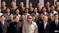 North Korean leader Kim Jong-il (in light jacket) poses with scientists and technicians at a purported satellite-control center after in April.