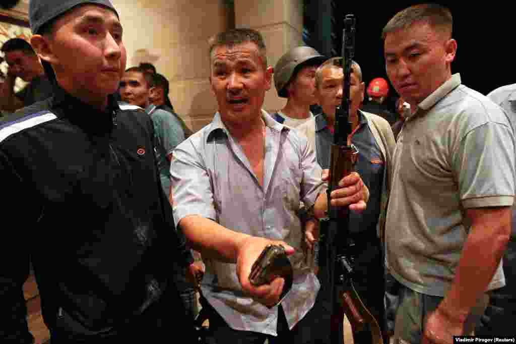 Supporters of Atambaev brandish an assault rifle and a clip of ammunition.