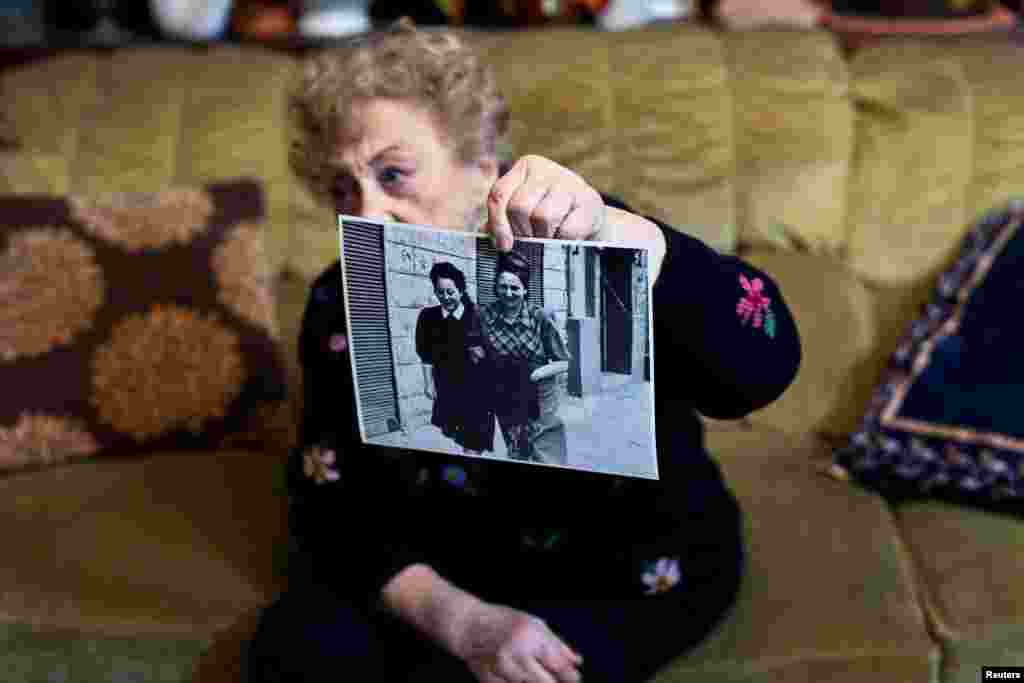 Jona Laks shows a photo of her and her older sister Chana, during an interview in her house in Tel Aviv, Israel January 21, 2020. Before her trip to Poland Jona Laks had recounted her arrival at Auschwitz. With her sisters and thousands of other Jews from the Lodz ghetto, she was transported by train. In cattle carts without windows, she thinks the journey lasted about three days. Being a twin helped her to survive, but it was also a reason for her to be subjected to pseudo-medical experiments.