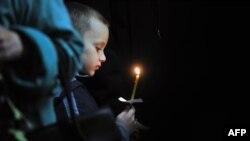 Мальчик держит свечу на акции по погибшим в авиакатастрофе в Египте. Новгород, 5 ноября 2015 года.