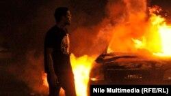 Egjipt - Një protestues shikon në drejtim të zyrave të Partisë për Drejtësi dhe Liri, të cilat janë përfshirë nga flakët
