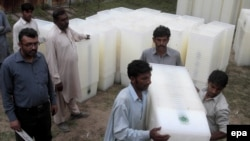 Workers at the election commission office in Lahore sort ballot boxes for Pakistan's upcoming general election.
