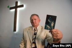 Священник Віталій Параскун показує фотографію, зроблену, коли він перебував у полоні. Він каже, що не боявся померти, коли його лякали стріляниною, і злякався, тільки коли погрожували роздробити коліно, тому що в камері був вагітний пацюк. Він не тримає зла на своїх мучителів. Він радий, що в полоні йому вдалося переконати чотирьох людей стати віруючими