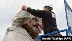 A worker covers the head of a statue of German philosopher, economist, political theorist and sociologist Karl Marx in Trier on April 13.