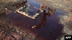 Ирак астанасында террорлық жарылыс болған жердегі қан аралас суға қарап тұрған бозбала бейнесі. (Көрнекі сурет.)