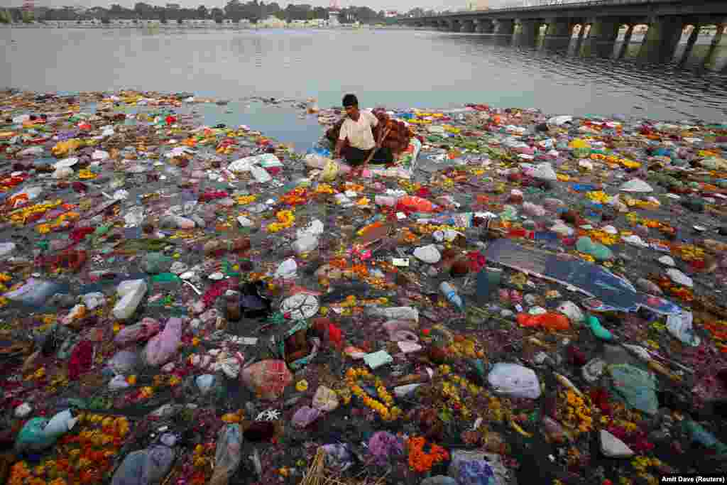 A man collects items thrown as offerings by worshippers into the Sabarmati River, a day after the immersion of idols of the Hindu god Ganesh, the deity of prosperity, in Ahmedabad, India. (Reuters/Amit Dave)