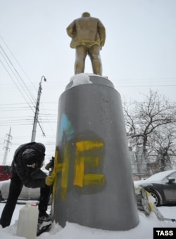 """Новосибирск, декабрь 2014 года. Сотрудник коммунальной службы отмывает памятник Ленину от надписи """"Слава Украине!"""", сделанной неизвестными на постаменте"""