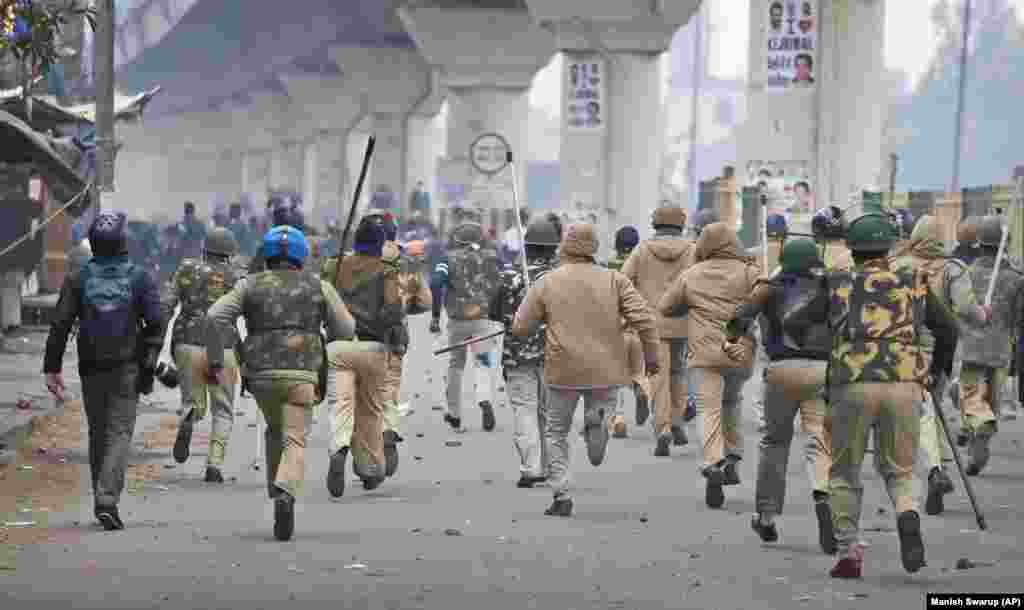 Policemen chase protesters during a protest in the Seelampur area of New Delhi on December 17.