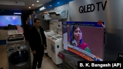 A Pakistani shopkeeper listens to Malala Yousafzai addressing a reception in Islamabad on March 29.