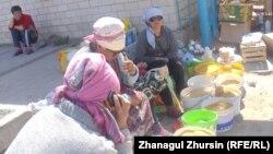 Женщины торгуют просом у входа на центральный рынок Шалкара. 4 мая 2013 года.