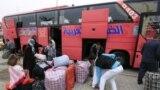 عائدون عراقيون من سوريا ينزلون حقائبهم من حافلة في بغداد