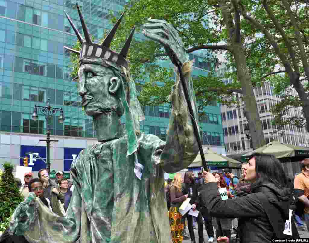 Three OWS activists make a papier-mache Statue of Liberty dance to music.
