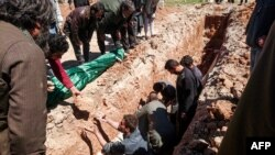 Syrians dig a grave to bury the bodies of victims of a suspected toxic gas attack that killed scores of people in opposition-held territory in Idlib Province earlier this month.