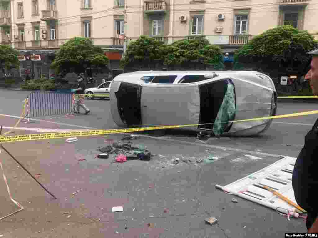 """An overturned car as day breaks in Tbilisi on June 21. Opposition politician Grigol Vashadze vowed""""We will meet again on Rustaveli Avenue at 19:00 [on June 21].We will need to agree on an action plan with people."""""""