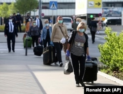 Romanian care workers accompanied by police and security arrive at the train station of Vienna's airport on May 11.