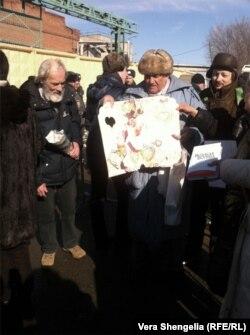 """Пожилой мужчина из """"Комитета 6 мая"""" держит огромную самодельную открытку с лебедями. Фото: Вера Шенгелия"""