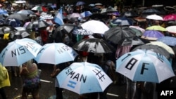 "People march towards Plaza de Mayo square under a heavy rain during the ""Marcha del silencio"" (March of Silence) called by Argentine prosecutors in memory of their late colleague Alberto Nisman in Buenos Aires on February 18, 2015. More than 400,000 peop"