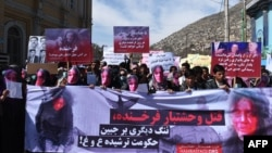 Members of the Afghan Solidarity Party wearing masks of the bloodied face of the woman who was lynched by a mob chant slogans during a protest against the attack in Kabul on March 23.